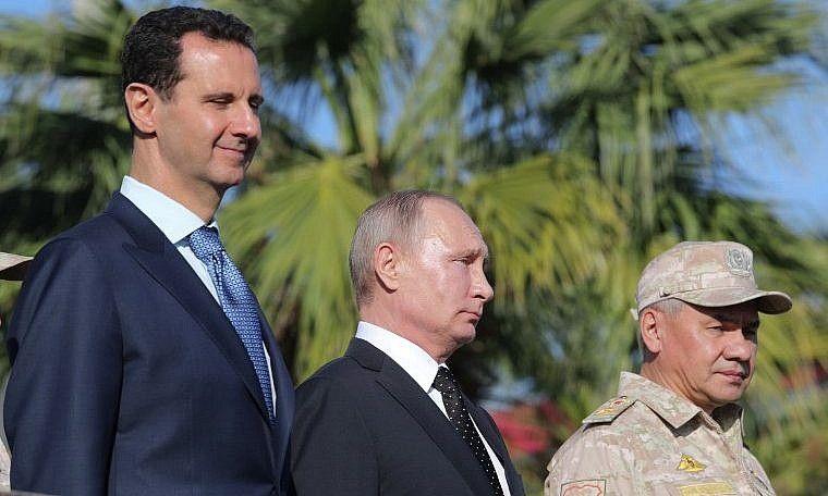 El presidente sirio Bashar al-Assad, a la izquierda, el presidente ruso Vladimir Putin y el ministro de Defensa ruso, Sergei Shoigu, inspeccionaron un desfile militar durante su visita a la base aérea rusa en Hmeimim, en la provincia de Latakia, noroeste de Siria, el 11 de diciembre de 2017. Mikhail Klimentyev / AFP)
