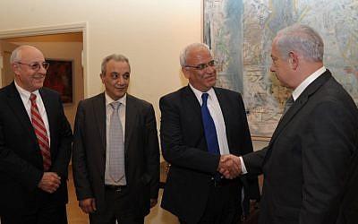 El primer ministro Benjamin Netanyahu le da la mano a Saeb Erekat en Jerusalén, abril de 2012. El ayudante de Netanyahu Yitzhak Molcho está a la izquierda y el jefe de seguridad de la Autoridad Palestina Majed Faraj está a la izquierda. (Amos Ben Gershom / GPO / Flash90)