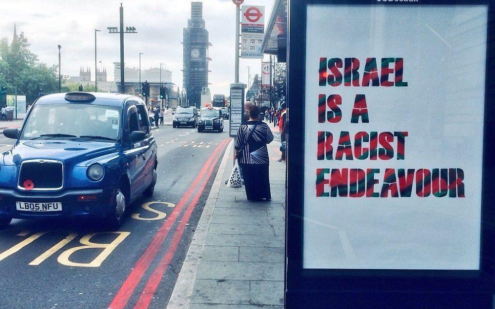 """Una parada de autobús de Londres desfigurada con un cartel no autorizado que decía: """"Israel es una empresa racista"""", que un grupo pro palestino presentó en protesta por la adopción de la definición de antisemitismo de IHRA por el Partido Laborista británico el 6 de septiembre de 2018. (Gorjeo)"""