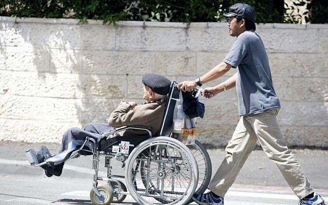 Ilustrativo: Una cuidadora filipina camina con un anciano israelí sentado en una silla de ruedas el 22 de abril de 2009. (Abir Sultan / Flash90)