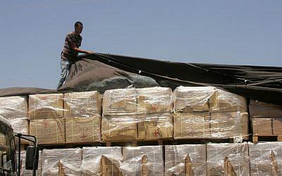 Un palestino revisa un camión cargado con ayuda humanitaria de los EE. UU. Cuando llega a la ciudad palestina de Rafah a través del cruce Kerem Shalom entre Israel y el sur de la Franja de Gaza el 6 de agosto de 2014.