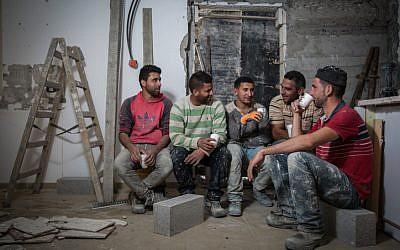 Trabajadores de la construcción palestinos de la aldea de Abadiya en Cisjordania, durante su descanso para tomar café en una casa en proceso de renovación en el asentamiento judío de Alon, al sur de Jerusalén, el 16 de febrero de 2016. (Hadas Parush / Flash90)