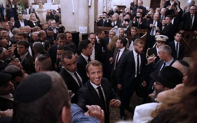 El presidente francés, Emmanuel Macron (C) saluda al salir de una ceremonia para conmemorar el llamado Año Nuevo judío, Rosh Hashaná, en la Gran Sinagoga de París el 4 de septiembre de 2018 (AFP PHOTO / POOL / YOAN VALAT)