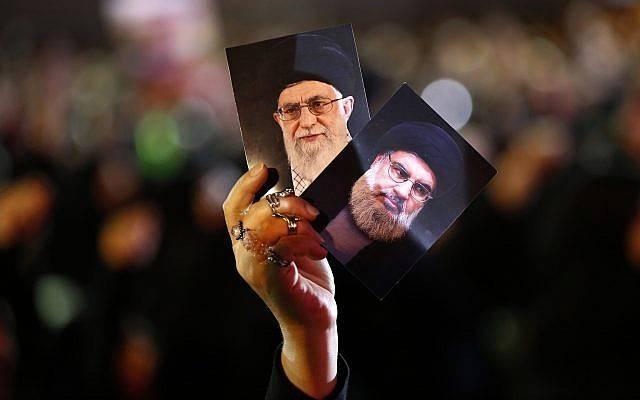 Un partidario de Hezbolá sostiene retratos del líder de Hezbolá, jeque Hassan Nasrallah, derecha, y el líder supremo iraní ayatolá Ali Khamenei, izquierda, durante las actividades para conmemorar el noveno Ashura, un ritual de 10 días para conmemorar la muerte del imán Hussein en un suburbio del sur de Beirut, Líbano, el 19 de septiembre de 2018. (AP Photo / Hussein Malla)