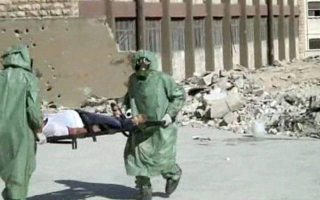 Foto ilustrativa: Esta imagen, de un video publicado el 18 de septiembre de 2013, muestra a sirios con trajes de protección y máscaras antigás conduciendo un simulacro sobre cómo tratar a las víctimas de un ataque con armas químicas, en Aleppo, Siria (AP)
