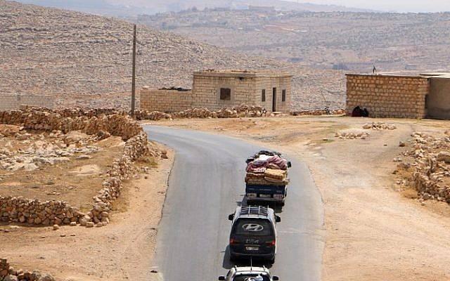 Los sirios desplazados que huyeron de las incursiones del régimen en vehículos con sus pertenencias arriban cerca de un campamento en Kafr Lusin cerca de la frontera con Turquía en la parte norte de la provincia siria de Idlib, controlada por los rebeldes, el 9 de septiembre de 2018. (AFP PHOTO / Aaref WATAD)