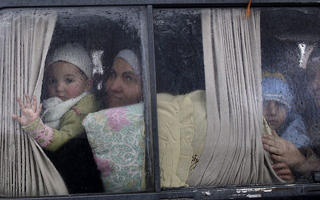 En esta foto de archivo del 20 de diciembre de 2012, los refugiados sirios, que huyeron de su hogar en Idlib debido a un ataque aéreo del gobierno, miran desde la ventanilla de un vehículo justo después de cruzar la frontera de Siria a Turquía en Cilvegozu, Turquía. (Foto AP / Muhammed Muheisen, Archivo)
