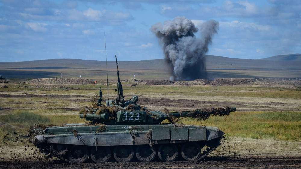 Un T-90 en el primer plano; una explosión por detrás