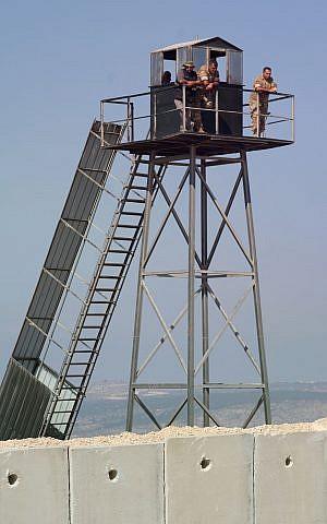 Miembros de las Fuerzas Armadas Libanesas vigilan la construcción de un muro fronterizo israelí desde una torre de vigilancia, cerca de la ciudad israelí de Rosh Hanikra, el 5 de septiembre de 2018. (Judah Ari Gross / Times of Israel)