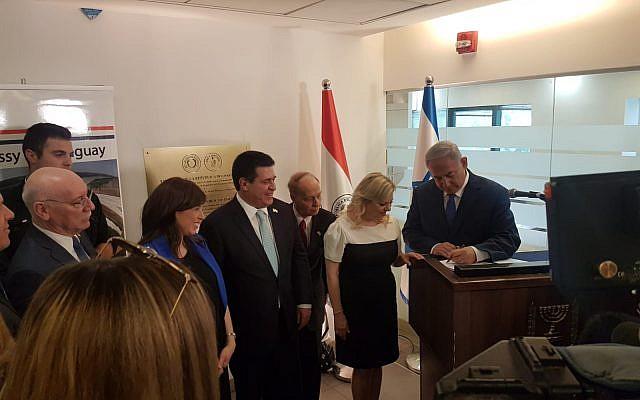 El primer ministro Benjamin Netanyahu, a la derecha, firma el libro de visitas en la nueva embajada de Paraguay en Jerusalén mientras su esposa Sara y el presidente de Paraguay Horacio Carter observan, el 21 de mayo de 2018 (Cortesía)