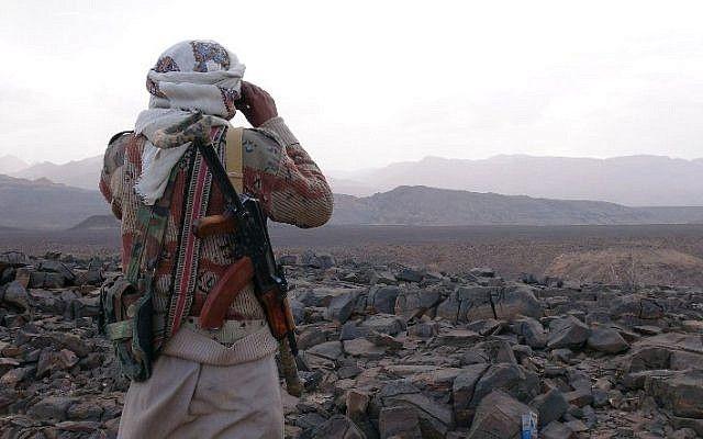 Un miembro armado de la tribu yemení de los Comités de Resistencia Popular que apoyan a las fuerzas leales al presidente fugitivo respaldado por Arabia Saudí, Abedrabbo Mansour Hadi, mira con prismáticos mientras continúan combatiendo a los rebeldes hutíes chiitas en el área de Jaadan, en la provincia de Marib al este de la capital, Sanaa, en 9 de mayo de 2015. (crédito de la foto: AFP / STR)