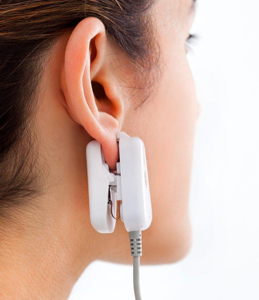 Los usuarios de GlucoTrack prueban los niveles de glucosa con un clip para la oreja conectado a una unidad de control portátil. Foto cortesía