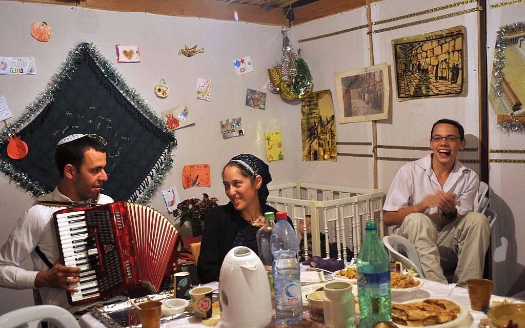 Ilustrativo: familia israelí comiendo en la sucá durante la segunda noche de Sucot en el barrio judío de la Ciudad Vieja de Jerusalem.(crédito de la foto: Serge Attal / Flash 90)