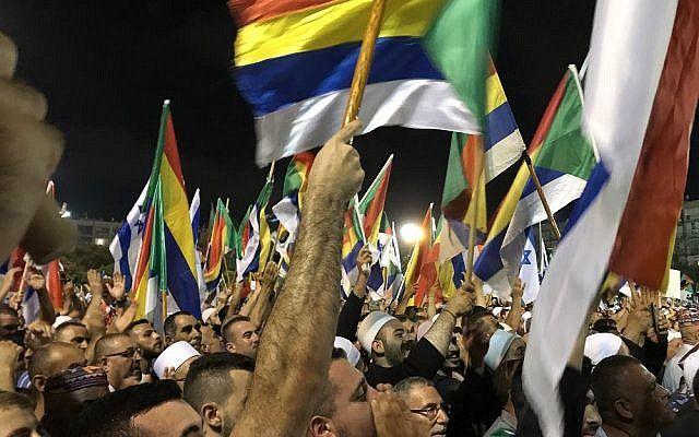 Manifestantes agitan banderas israelíes y drusas en una manifestación contra la ley del estado-nación, en la plaza Rabin de Tel Aviv el 4 de agosto de 2018. (Personal de Luke Tress / Times of Israel)