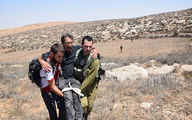 Un activista de izquierda herido siendo escoltado por otro activista y un soldado de las FDI después de ser presuntamente atacado por colonos, cerca del asentamiento de Mitzpeh Yair en Cisjordania, el 25 de agosto de 2108. (B'Tselem)
