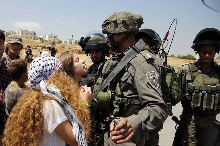 Ahed Tamimi (C), entonces de 16 años, instigando las fuerzas israelíes en la aldea de Nabi Saleh, al norte de Ramallah, después de la violencia islamista propia de las oraciones del viernes, en solidaridad con los terroristas palestinos en las cárceles israelíes, el 12 de mayo de 2017 . (AFP PHOTO / ABBAS MOMANI)