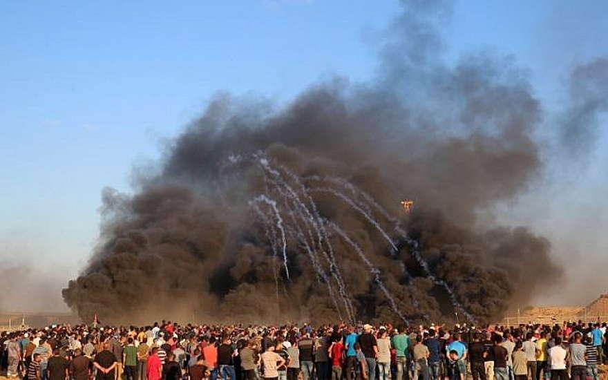 El 12 de octubre de 2018, terroristas palestinos se reúnen en el humo que se alza al quemar llantas cuando las fuerzas israelíes lanzan botes de gas lacrimógeno a la frontera entre Israel y Gaza, al este de la ciudad de Gaza. (Foto de SAID KHATIB / AFP)