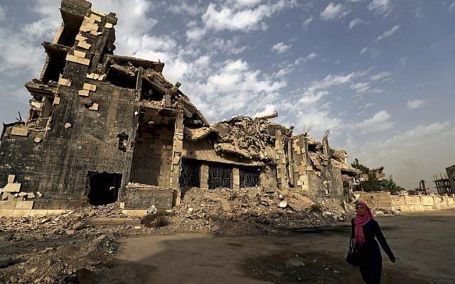 Una mujer pasa junto a un edificio dañado en la ciudad siria de Raqqa el 13 de octubre de 2018. (Delil Souleiman / AFP)