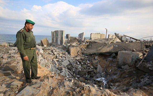 Un oficial de Hamas camina sobre escombros después de un ataque aéreo israelí en represalia cerca de la ciudad de Rafah, en el sur de la Franja de Gaza, después de que un cohete impactara en una casa en la ciudad israelí de Beerseba el 17 de octubre de 2018. (Said Khatib / AFP)