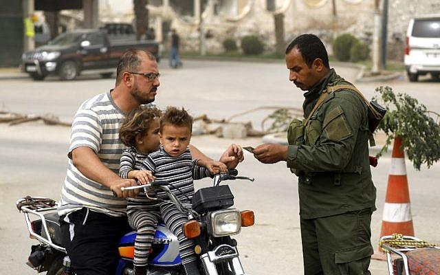 Un miembro de las fuerzas de seguridad locales del consejo civil de Raqqa verifica los documentos de identificación de un hombre que viajaba en una motocicleta con dos niños en un puesto de control que aseguraba la entrada de vehículos a la ciudad del este de Siria y al antiguo bastión del Estado Islámico (IS), el 16 de octubre de 2018. ( Delil Souleiman / AFP)