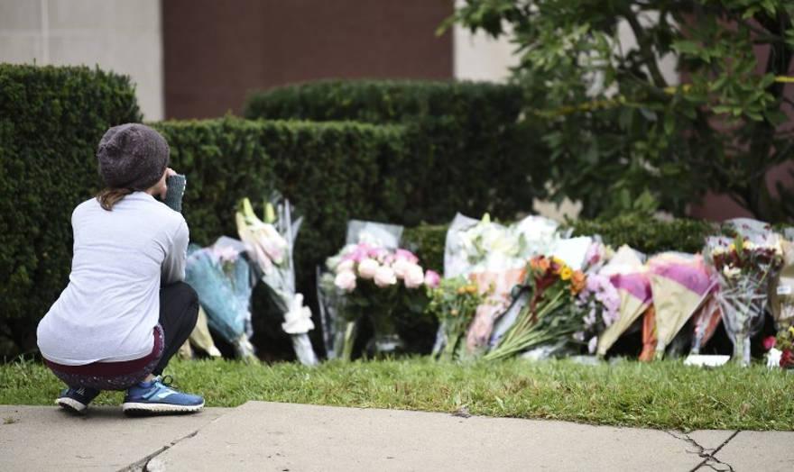 El día después de un tiroteo mortal, una mujer mira las flores como parte de un memorial fuera de la sinagoga del Árbol de la Vida, el 28 de octubre de 2018. (Brendan SMIALOWSKI / AFP)
