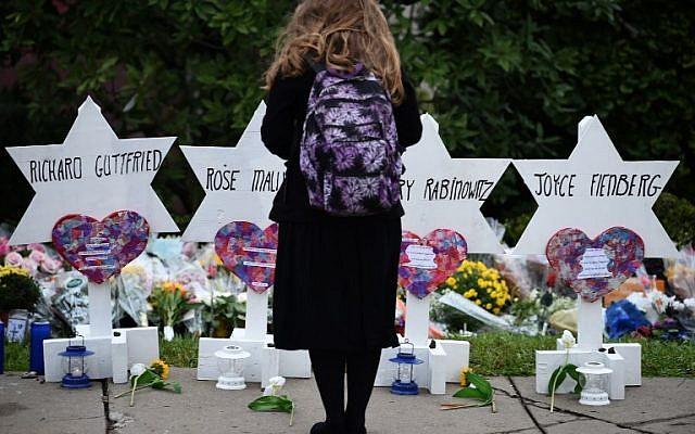 Una mujer se para en un monumento conmemorativo de las víctimas de un tiroteo mortal en la sinagoga del Árbol de la Vida en el vecindario de Squirrel Hill en Pittsburgh, el 27 de octubre de 2018. (SMIALOWSKI / AFP)