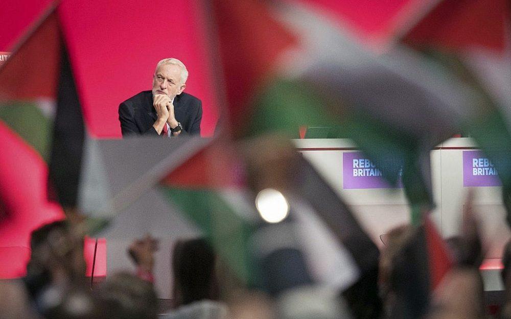 El líder laborista del Reino Unido, Jeremy Corbyn, se sienta en el escenario mientras los simpatizantes ondean banderas palestinas durante la conferencia anual del partido en Liverpool, Inglaterra, el 25 de septiembre de 2018. (Stefan Rousseau / PA a través de AP)