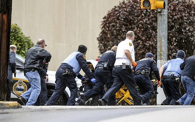 Las fuerzas del orden público corrieron con una persona en una camilla en la escena donde varias personas recibieron disparos, el sábado 27 de octubre de 2018, en la Congregación del Árbol de la Vida en el vecindario Squirrel Hill de Pittsburgh. (Alexandra Wimley / Pittsburgh Post-Gazette a través de AP)