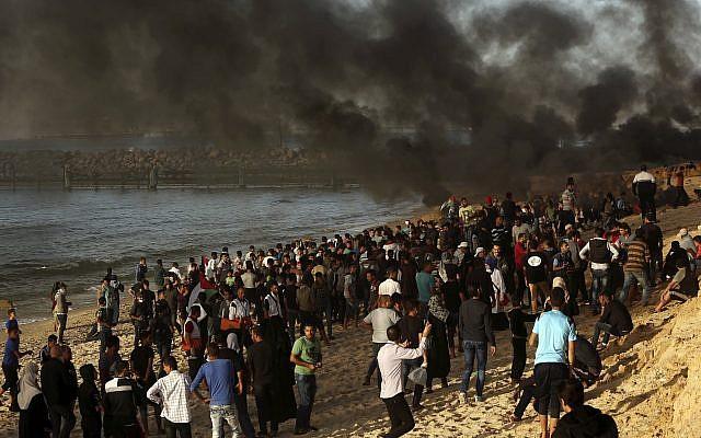 Los palestinos se reúnen en la playa mientras otros queman neumáticos cerca de la cerca de la frontera de la Franja de Gaza con Israel cerca de Beit Lahiya, , 29 de octubre de 2018. (Adel Hana / AP)