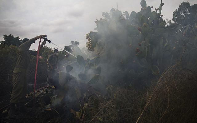 Soldados israelíes apagan un incendio iniciado por un globo con tela ardiente anexada lanzada por palestinos desde la Franja de Gaza en Moshav Kfar Maimon, 1 de octubre de 2018. (AP Photo / Tsafrir Abayov)
