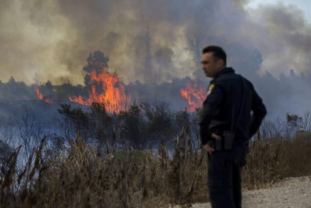 Un policía israelí observa un incendio iniciado por un globo con tela ardiente anexada lanzada por palestinos desde la Franja de Gaza en el parque natural de Karmia, cerca de Israel y la frontera de Gaza, el jueves 11 de octubre de 2018. (AP / Tsafrir Abayov)