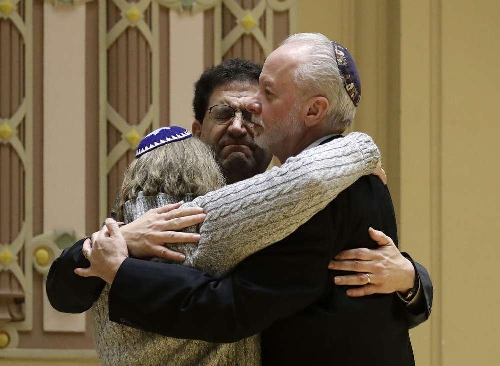 El rabino Jeffrey Myers, a la derecha, de Árbol de la Vida abraza al rabino Cheryl Klein, a la izquierda, de la Congregación Dor Hadash y el rabino Jonathan Perlman durante una reunión comunitaria celebrada tras un tiroteo mortal en la Sinagoga Árbol de la Vida en Pittsburgh, 28 de octubre de 2018. (Foto AP / Matt Rourke)