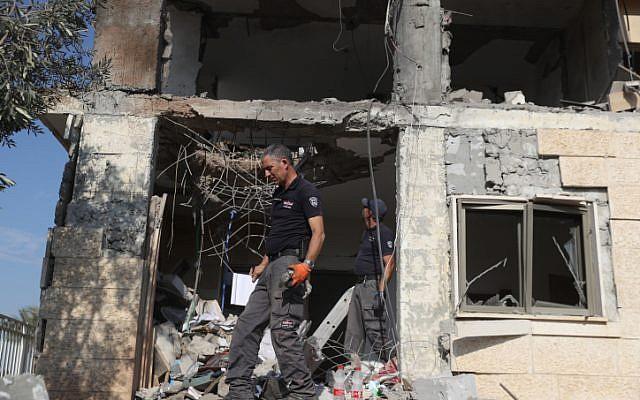 Las fuerzas de seguridad israelíes inspeccionan un edificio que fue alcanzado por un cohete disparado desde la Franja de Gaza en la ciudad de Beersheba, sur de Israel, el 17 de octubre de 2018. (Yonatan Sindel / Flash90)