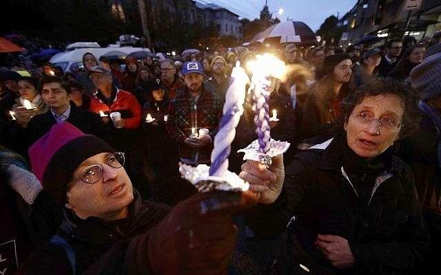 La gente enciende velas mientras se reúnen para una vigilia después de un tiroteo mortal en la Congregación Árbol de la Vida, en el vecindario de Squirrel Hill de Pittsburgh, el sábado 27 de octubre de 2018. (AP / Matt Rourke)