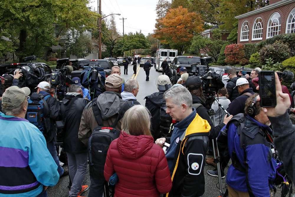 Una multitud de medios de comunicación esperan en la calle a dos cuadras de la Sinagoga Árbol de la Vida en Pittsburgh, donde un tirador mató a 11 personas el sábado 27 de octubre de 2018. (AP / Gene J. Puskar)