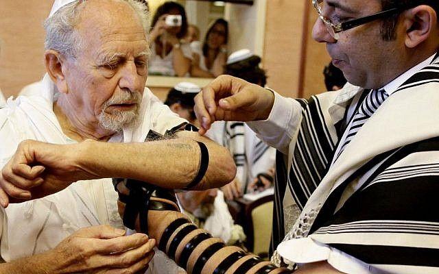 Se envuelve tefilín a un sobreviviente del Holocausto mientras celebra su bar mitzvah (crédito de foto: Flash 90)