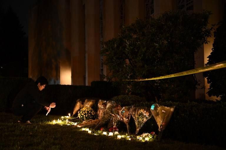 Un hombre se arrodilla para encender una vela debajo de un cordón policial fuera de la Sinagoga Árbol de la Vida en Pittsburgh, después de un tiroteo que dejó 11 muertos el 27 de octubre de 2018 (Brendan Smialowski / AFP)