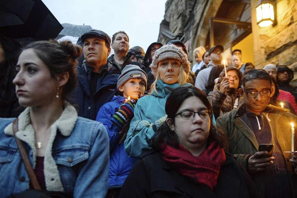 La gente se para en las escaleras de la Sexta Iglesia Presbiteriana mientras la multitud se desplaza cuesta arriba por la colina y por la calle para ver unas cuadras desde donde un hombre armado disparó y mató a 11 fieles en la sinagoga de la Congregación Árbol de la Vida el sábado 27 de octubre de 2018, en el Squirrel Hill sección de Pittsburgh, Pennsylvania.(Stephanie Strasburg / Pittsburgh Post-Gazette a través de AP)