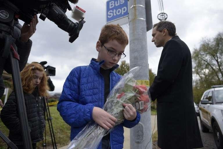 Un niño lleva a flores a un memorial el 28 de octubre de 2018, cerca de la sinagoga Árbol de la Vida, luego de que un tiroteo dejó 11 personas muertas en el vecindario de Squirrel Hill en Pittsburgh el 27 de octubre de 2018 (Dustin Franz / AFP)