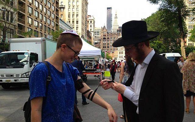 Ilustrativo: un representante de Jabad coloca filacterias en un transeúnte en Union Square de Nueva York el viernes 19 de junio de 2015 (Facebook)