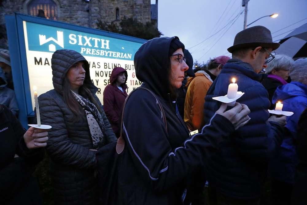 Una multitud sostiene velas en el césped de la Sexta Iglesia Presbiteriana en la intersección de Murray Ave.y la avenida Forbes.en la sección Squirrel Hill de Pittsburgh, Pensilvania, durante una vigilia conmemorativa por las víctimas del tiroteo en la Sinagoga Árbol de la Vida, donde un hombre armado disparó y mató a 11 fieles el sábado 27 de octubre de 201. (AP Photo / Gene J. Puskar)