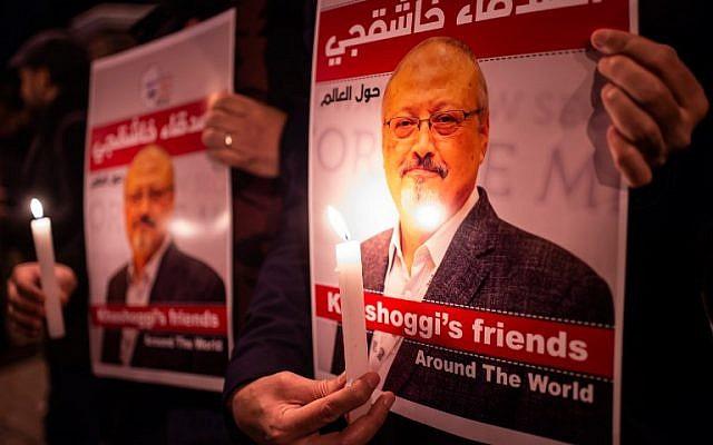 La gente sostiene carteles que representan al periodista saudita Jamal Khashoggi y encendieron velas durante una reunión fuera del consulado de Arabia Saudita en Estambul, el 25 de octubre de 2018. (Yasin Akgul / AFP)