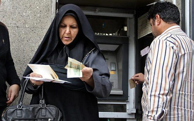 La gente retiró dinero de un cajero automático en el gran bazar de la capital iraní, Teherán, el 3 de noviembre de 2018. (ATTA KENARE / AFP)