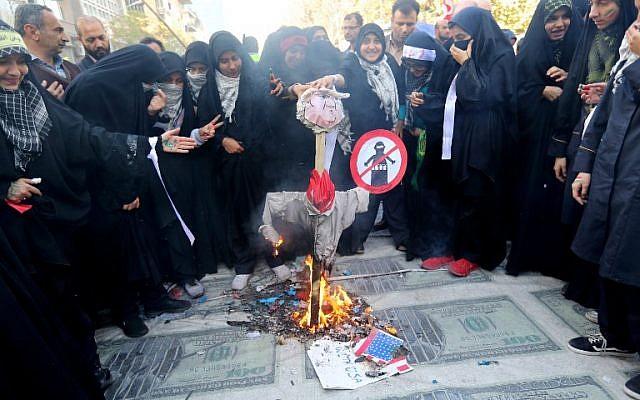 Los manifestantes iraníes queman una efigie de la red presidencial de Estados Unidos colocada en enormes impresiones de imágenes de billetes de 100 dólares estadounidenses durante una manifestación frente a la antigua embajada de Estados Unidos en la capital, Teherán, el 4 de noviembre de 2018, para conmemorar el aniversario de su asalto por parte de los manifestantes estudiantiles que provocaron Crisis de rehenes en 1979. (ATTA KENARE / AFP)