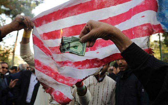 En vísperas de las nuevas sanciones por parte de Washington, los manifestantes iraníes queman un billete de un dólar y una bandera improvisada de Estados Unidos durante una manifestación frente a la antigua Embajada de los Estados Unidos en la capital iraní de Teherán el 4 de noviembre de 2018, que marca el aniversario de su asalto por parte de estudiantes manifestantes que activaron Una crisis de rehenes en 1979. (ATTA KENARE / AFP)
