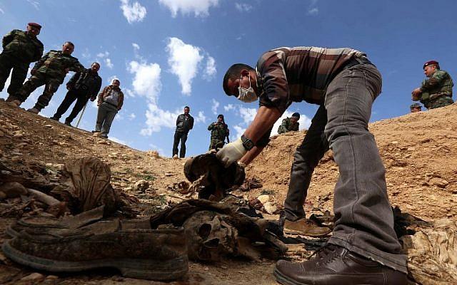 En esta foto de archivo tomada el 3 de febrero de 2015, Yazidis busca a familiares desaparecidos en los restos de personas asesinadas por jihadistas del Estado Islámico cerca de la aldea iraquí de Sinuni. (Safin HAMED / AFP)