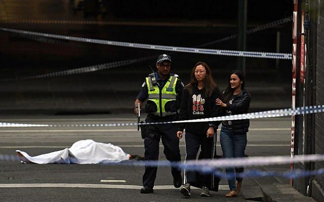 Un oficial de policía aleja a las personas de la escena del crimen mientras se ve un cuerpo cubierto con una sábana blanca en Melbourne el 9 de noviembre de 2018 (William West / AFP)
