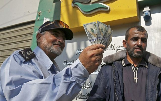 Un hombre palestino muestra su dinero luego de recibir su salario en Rafah, en el sur de la Franja de Gaza, el 9 de noviembre de 2018. (Foto de SAID KHATIB / AFP)