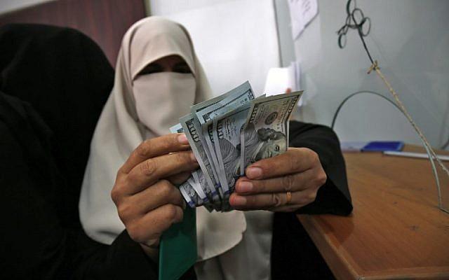 Una mujer palestina cuenta su dinero luego de recibir su salario en Rafah, en el sur de la Franja de Gaza, el 9 de noviembre de 2018. (Said Khatib / AFP)