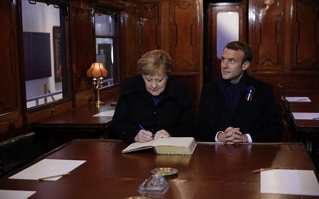 El presidente francés, Emmanuel Macron, y la canciller alemana, Angela Merkel, firman el Libro de Oro el 10 de noviembre de 2018, mientras se sientan en el vagón del tren donde se firmó el armisticio que terminó la Guerra Mundial en el desmonte de Rethondes (el Claro del Armisticio) en Compiegne, norte Francia. (Philippe Wojazer / Pool / AFP)